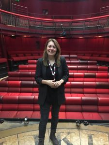 Image shows Trish on the stage with red auditorium seating behind her at The Egg Theatre, Bath